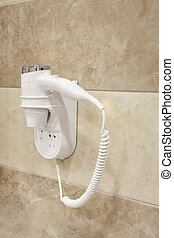 Hair dryer hanging on wall in bathroom of a hotel