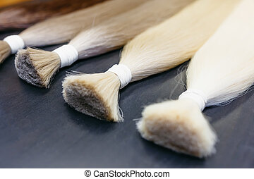hair extensions of five colors on a dark background....