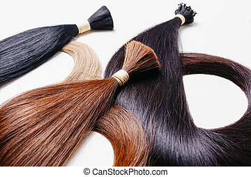 hair extensions of three colors on a white background. ...
