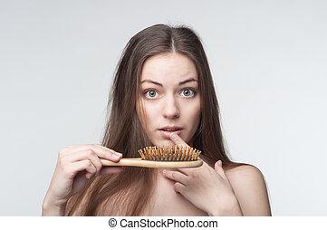 Hair loss - one young beautiful woman waves through hair...