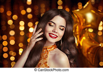 Hair. Makeup. Elegant brunette. Beautiful happy smiling woman portrait with red lips makeup and healthy long wavy hairstyle posing over golden srat balloons, Christmas boker background.