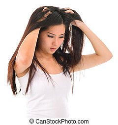 Hair problem - Young Asian girl scratches her hair on white...