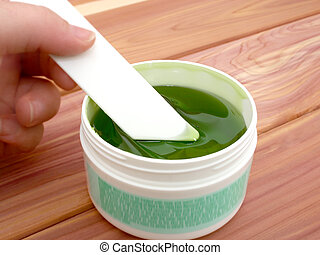 Hair Remover - Jar of sticky green hair remover. Shallow dof...