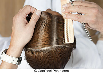 hair salon - high angle view of hairdresser using comb