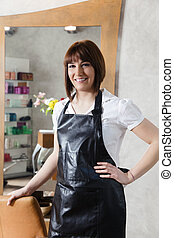 hair salon - portrait of young adult hairstylist looking at...