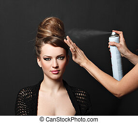 Hair spray, woman over black. Studio shot.
