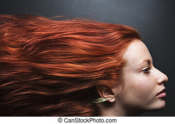 Pretty redhead young woman profile with hair streaming out behind her.