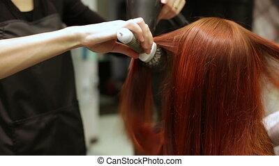 Hair styling comb and hair dryer at beauty salon - Pulling...
