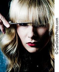 Hair stylist - A hair stylist cutting her own hair,...