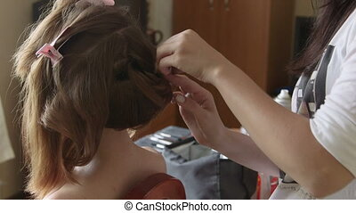 Hair stylist at work - Stylist pinning up a bride's...