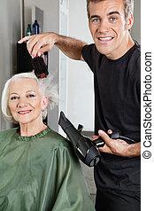 Hair Stylist Blow Drying Senior Woman's Hair - Portrait of...