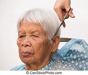 cutting senior woman's gray hair - Hair stylist cutting...