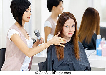 Hair stylist does hair style of woman in hairdressing salon. Concept of fashion and beauty