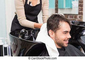 Hair stylist drying mans hair at the hair salon