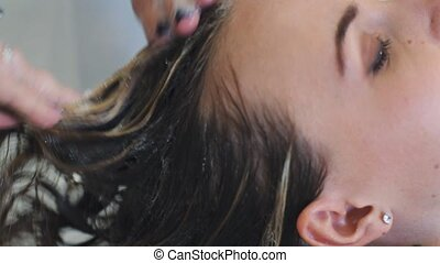 Hair stylist in gloves washing blond dyed woman head over...
