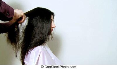 Hair stylist ironing long hair - Professional stylist...