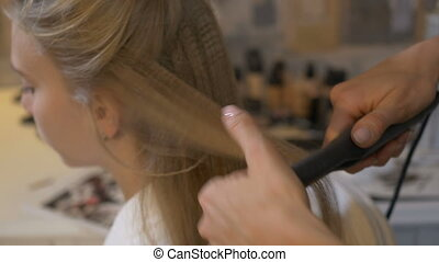 Hair stylist makes hairstyle to girl - Beautiful girl is...