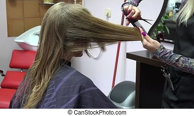 hair stylist making new haircut to blonde woman in salon. 4K...