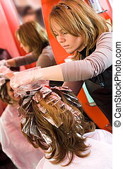 Hair-stylist - Woman\'s hair being painted at the hair...