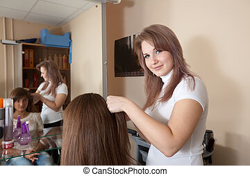 stylist works on woman hair