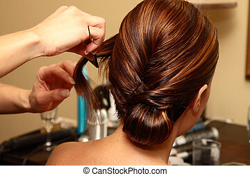 Hair Stylist - Young bride sitting while a hair stylist is...