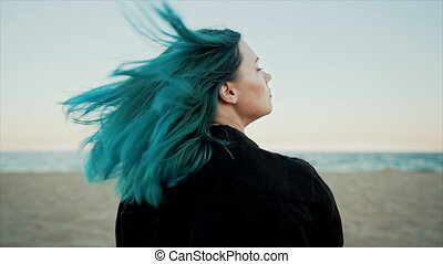 Hair toss of unique woman with teal blue or turquoise dyed hairstyle on sea beach background. Portrait of hipster girl with unusual hair enjoying summertime alone, demonstrate her fresh color. Slow.