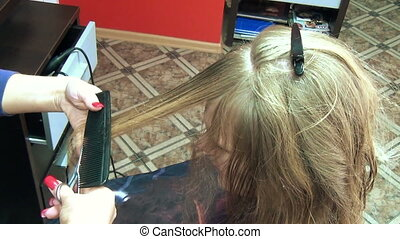 hair trim tips - hairdresser spraying water from red bottle...
