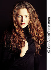 Portrait of a charming fashion model with beautiful curly hair. Over black background.