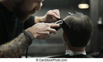 Haircut of dark haired bearded man in barbershop - Attentive...