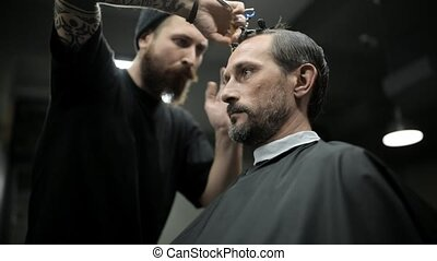 Haircut of dark haired bearded man in barbershop - Stylish...