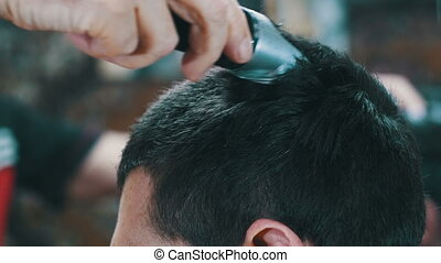 Haircutter Cuts Young Man with Clipper - Haircutter Cuts...