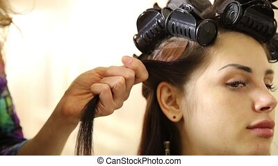 Hairdo. hairdresser's hands to work on client's hair at...