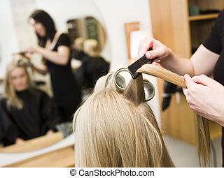 Hairdresser and customer - Hairdresser in action with blond ...