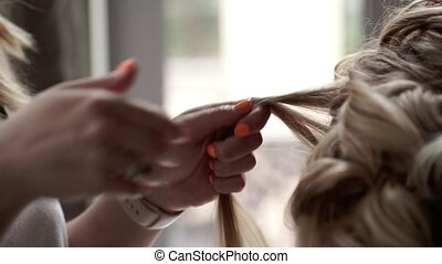 Hairdresser at work makes hairstyle