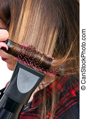 Hairdresser blow-drying a clients hair