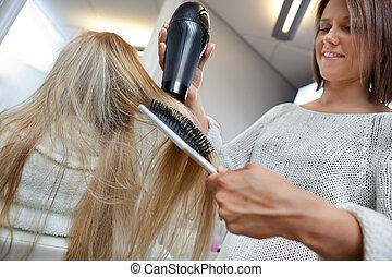 Hairdresser Blow Drying Hair Of Female