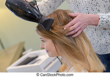hairdresser blow drying hair