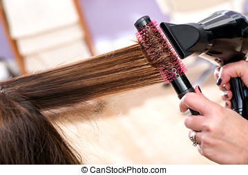 Hairdresser blow drying long brown hair