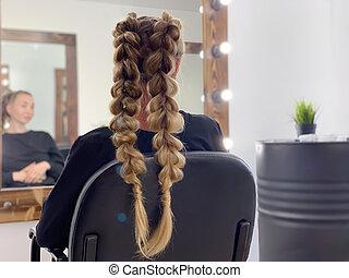 Hairdresser braiding woman's hair in hairdressing salon