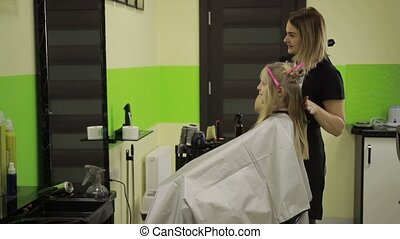 Hairdresser brushing girl's hair in beauty salon.