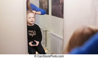 hairdresser combing her hair of cute little girl