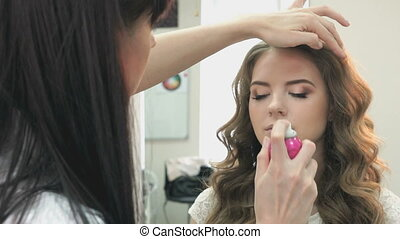 Hairdresser combing the hair of a beautiful model