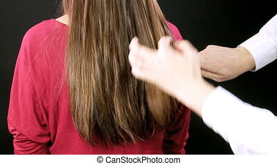 Hairdresser combing wet hair - Straight long hair being...
