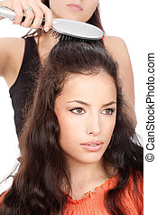 hairdresser combing woman's long black hair
