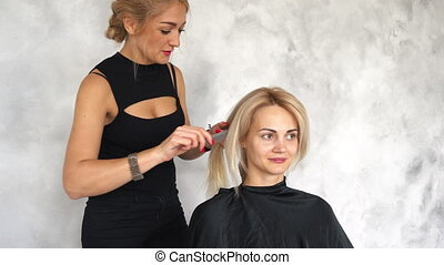 Hairdresser combs hair before styling in beauty salon
