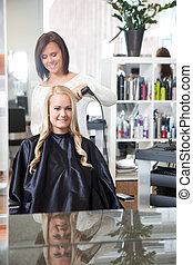 Hairdresser Curling Young Woman's Hair