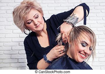 Hairdresser cut hair of woman
