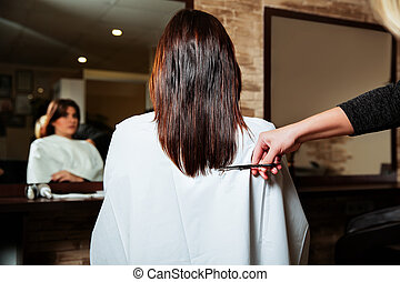 Hairdresser cut long ends to yuong woman. Hairdressing...
