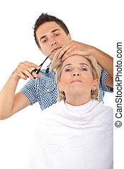 Hairdresser cut senior woman hair over white background