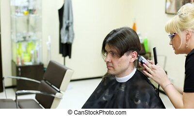 Hairdresser cuts hair on nape to man with long hair by...